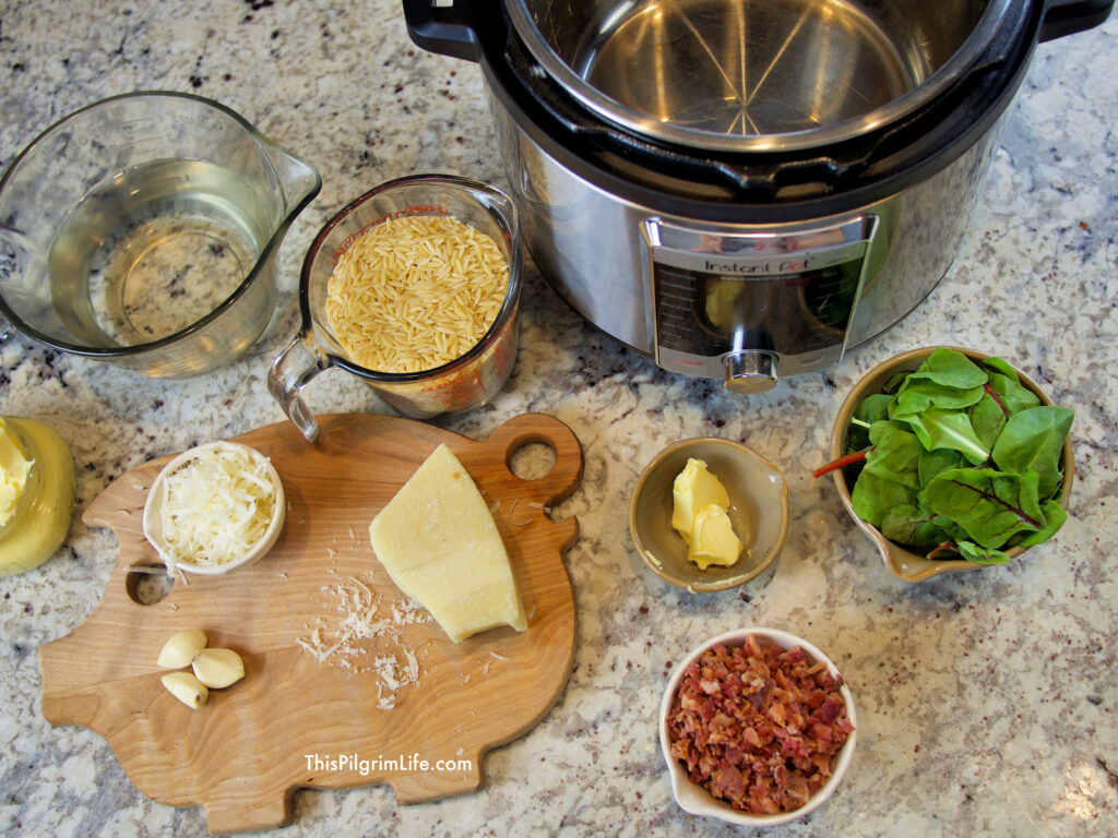 Garlic orzo ingredients: orzo, butter, garlic, parmesan cheese, greens, bacon, water, and salt.