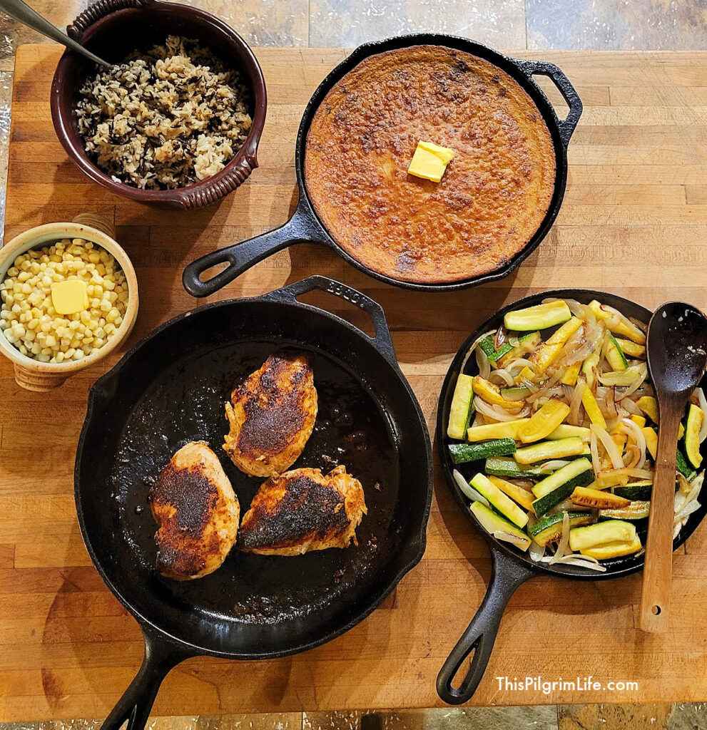 Blackened chicken with cornbread, rice, corn, and sautéed vegetables.